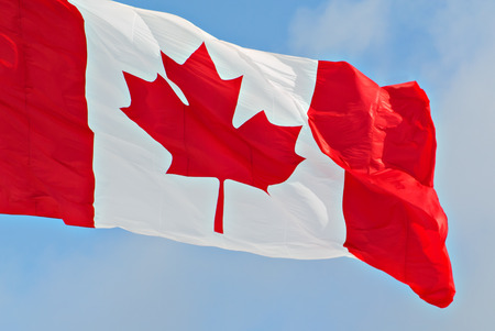 Close up of a Canadian flag flying against a blue sky