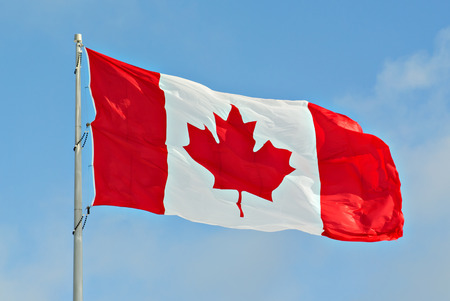 first day: Flag of Canada flying against a blue sky     Stock Photo