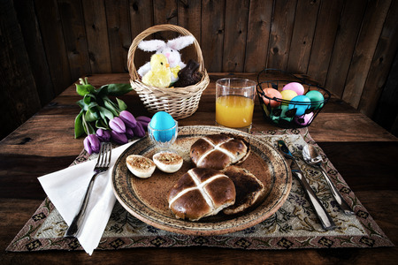 cross processed: A place setting for Easter Breakfast of eggs and hot cross buns   Processed in a lightly bleached rustic retro style  Stock Photo