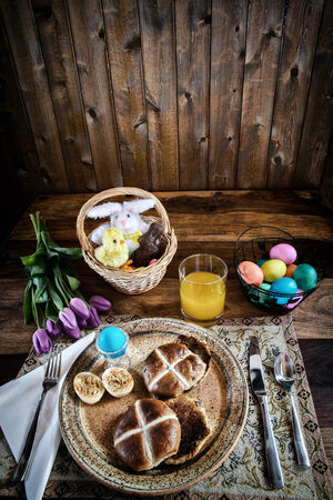 A place setting for Easter Breakfast of eggs and hot cross buns   Processed in a lightly bleached rustic retro style   Room for Copy Space