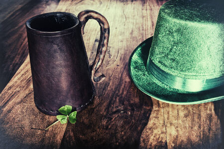 patrick: A Saint Patricks Day background featuring a historic leather mug, green hat, and a shamrock.  Processed for a retro faded look.