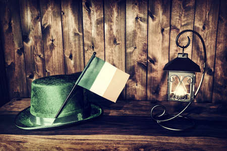 A Saint Patricks Day background featuring the flag of Ireland and a green hat bathed in lantern light.  Processed for a rustic retro faded look.