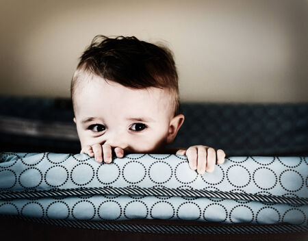 A small toddler boy peers over the top of his crib or playpen with a mischievious look    Processed for an aged vintage retro look    Imagens