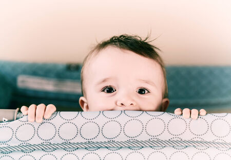 A small toddler boy peers over the top of his crib or playpen with a happy expression Processed for an aged vintage retro look