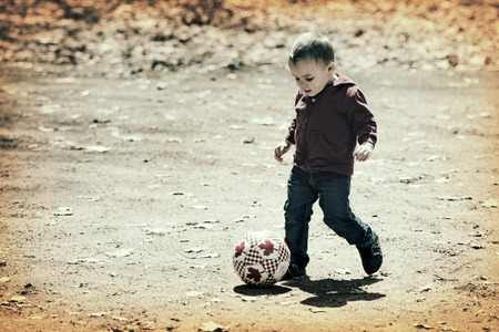 A small boy takes a kick at the soccer ball as he enjoys some time outdoors on a brisk early spring or late fall day   Processed for an vintage retro look
