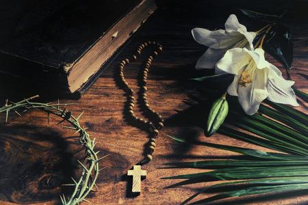 De Triumph, Passie, kruisiging en opstanding. Iconische christelijke symbolen die gebeurtenissen van Palmzondag tot Pasen rusten op een rustieke tafel samen met een 19e eeuwse antieke bijbel - palmtak, kroon van doornen, kruis en witte lelie.