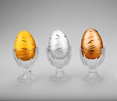 silver medal: Decorative metallic Easter eggs in cups in a row in bronze, silver, and gold colors.   Stock Photo