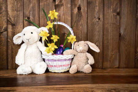 Easter background with room for copy space containing a plush lamb, bunny, and chick holding a basket of Easter eggs and flowers.    photo