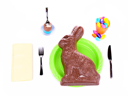 giant easter egg: A meal made entirely of holiday sweets, featuring an oversized out of scale chocolate Easter bunny.  A visual concept and commentary on overdoing it on the sweets during holidays.     Stock Photo