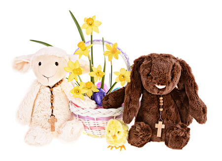 A plush lamb, bunny, wearing cross pendants holding a basket of Easter eggs and flowers.  Isolated on a white background.     photo