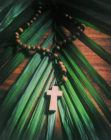 Palmzondag stilleven - Een gerolde olijf houten kruis of rozenkrans rust op een palmtak op de top van een rustieke tafel. Verwerkt voor een oude vintage look.