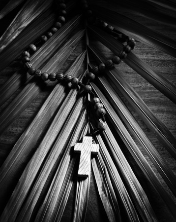 palm sunday: Palm Sunday still life - A beaded olive wood cross or rosary rests upon a palm branch on top of a rustic table.  Presented in Black and White.  Stock Photo