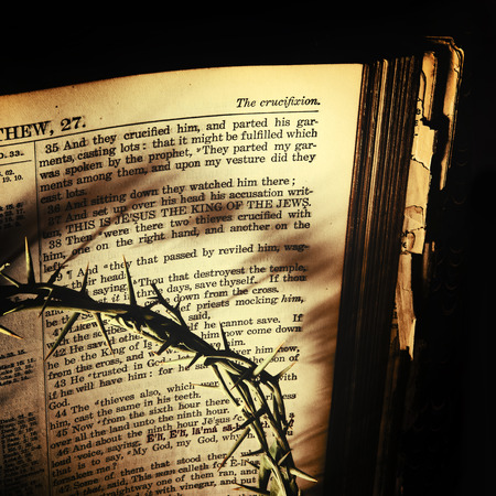 thorn: The Crown of Thorns casts dark shadows over an antique 19th century family bible open to St. Matthews recounting the cruxifiction of Christ. Processed for an aged vintage look.