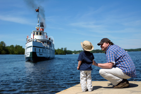 come home: A father and son watch an historic19th century coal fired steam ship come home to port