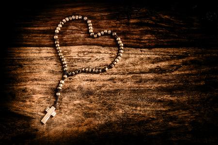 Een eenvoudige kralen olijf houten kruis of rozenkrans rust op een rustieke tafel in de vorm van een hart gelegd. Symbolen van Christus en de liefde. Verwerkt voor een rustieke uitstraling met een dramatische vignet.