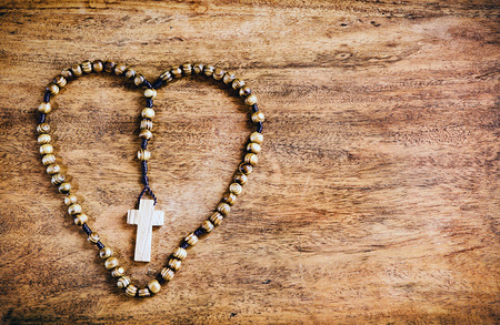 A simple beaded olive wood cross or rosary rests upon a rustic table laid out in the shape of a heart. Symbols of Christ & love.    Processed for a rustic look.