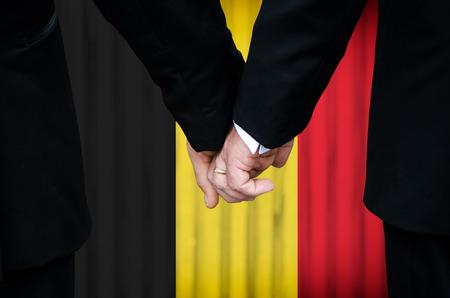 Twee homoseksuele mannen elkaar een hand geven voordat een huwelijk altaar met een overlay van de vlag kleuren van België, hebben onlangs wettelijk gehuwd onder het homohuwelijk wetgeving van dat land. Stockfoto