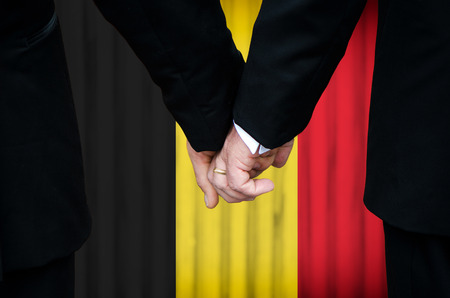 Two gay men stand hand in hand before a marriage altar featuring an overlay of the flag colors of Belgium, having just been legally married under the Same-Sex Marriage legislation of that country.    photo