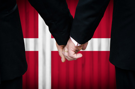 Two gay men stand hand in hand before a marriage altar featuring an overlay of the flag colors of Denmark, having just been legally married under the Same-Sex Marriage legislation of that country.    photo