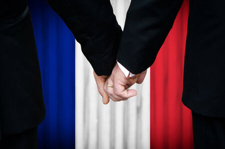 Two gay men stand hand in hand before a marriage altar featuring an overlay of the flag colors of France, having just been legally married under the Same-Sex Marriage legislation of that country.    photo