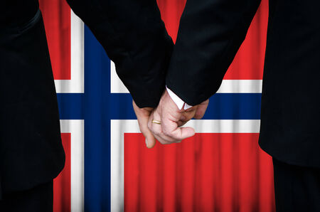 Two gay men stand hand in hand before a marriage altar featuring an overlay of the flag colors of Norway, having just been legally married under the Same-Sex Marriage legislation of that country.    photo