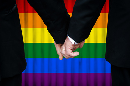 same sex: Married with Pride - two gay men stand hand in hand before a marriage altar featuring an overlay of pride flag colors,  having just been legally married under Same-Sex Marriage legislation.