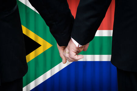Two gay men stand hand in hand before a marriage altar featuring an overlay of the flag colors of South Africa, having just been legally married under the Same-Sex Marriage legislation of that country.    photo