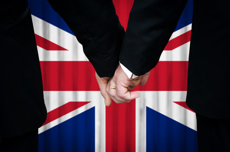 Two gay men stand hand in hand before a marriage altar featuring an overlay of the Union Flag, having just been married within a United Kingdom country with legalized Same-Sex Marriage legislation.    photo