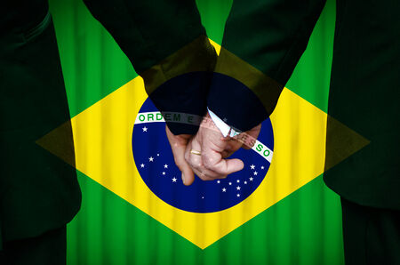 Two gay men stand hand in hand before a marriage altar featuring an overlay of the flag colors of Brazil, having just been legally married under the Same-Sex Marriage legislation of that country.    photo