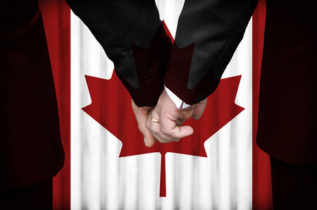 Two gay men stand hand in hand before a marriage altar featuring an overlay of the flag colors of Canada, having just been legally married under the Same-Sex Marriage legislation of that country.    photo