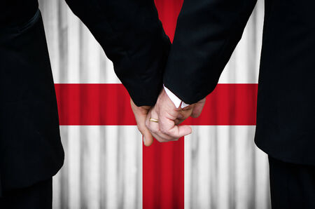 Two gay men stand hand in hand before a marriage altar featuring an overlay of the flag colors of England, having just been legally married under the Same-Sex Marriage legislation of that country.    photo