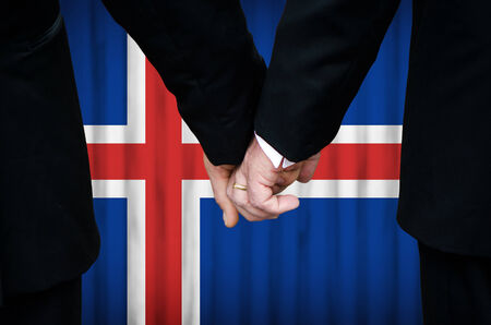 Two gay men stand hand in hand before a marriage altar featuring an overlay of the flag colors of Iceland, having just been legally married under the Same-Sex Marriage legislation of that country.    photo