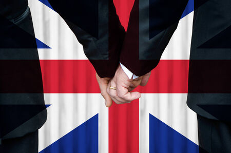 Great Britain (sans Ireland) -   two gay men stand hand in hand in wedlock before a marriage altar featuring an overlay of a historic flag of Great Britain lacking St. Patricks insignia.  As of April 2014, Northern Ireland has not introduced legislation  photo