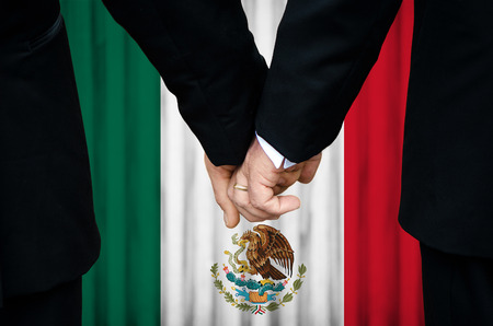 Two gay men stand hand in hand before a marriage altar featuring an overlay of the flag colors of Mexico, having just been married within a jurisdiction of that country that has legalized Same-Sex Marriage legislation.    photo