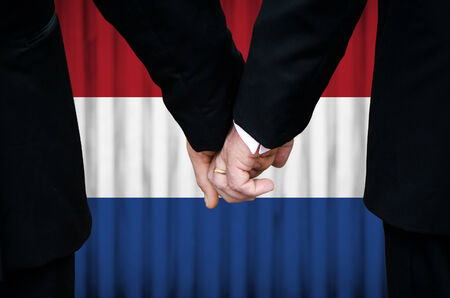 Two gay men stand hand in hand before a marriage altar featuring an overlay of the flag colors of the Netherlands, having just been legally married under the Same-Sex Marriage legislation of that country.    photo