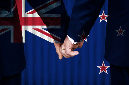 Two gay men stand hand in hand before a marriage altar featuring an overlay of the flag colors of New Zealand, having just been legally married under the Same-Sex Marriage legislation of that country.    photo