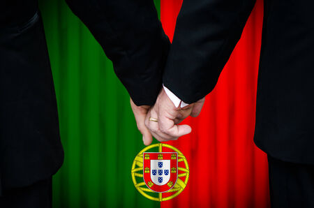 Two gay men stand hand in hand before a marriage altar featuring an overlay of the flag colors of Portugal, having just been legally married under the Same-Sex Marriage legislation of that country.    photo