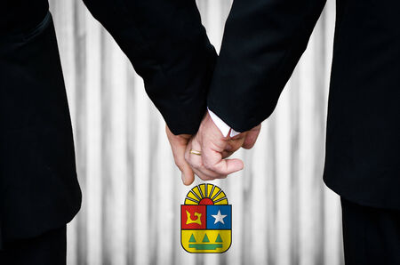 Two gay men stand hand in hand before a marriage altar featuring an overlay of the insignia of Quintana Roo - Mexico, having just been legally married under the Same-Sex Marriage legislation of that Mexican State.    photo