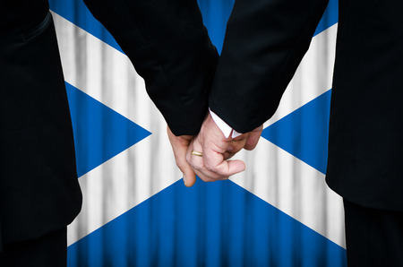 Two gay men stand hand in hand before a marriage altar featuring an overlay of the flag colors of Scotland, having just been legally married under the Same-Sex Marriage legislation of that country.    photo