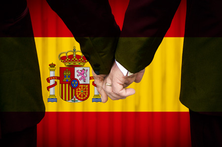 Two gay men stand hand in hand before a marriage altar featuring an overlay of the flag colors of Spain, having just been legally married under the Same-Sex Marriage legislation of that country.    photo