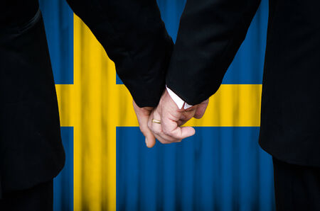 Two gay men stand hand in hand before a marriage altar featuring an overlay of the flag colors of Sweden, having just been legally married under the Same-Sex Marriage legislation of that country.    photo