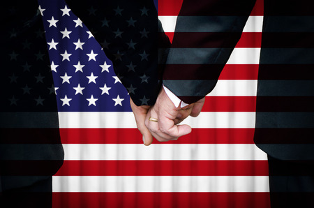 Two gay men stand hand in hand before a marriage altar featuring an overlay of the flag of the United States of America, having just been married within a State of that country that has legalized Same-Sex Marriage legislation.    photo