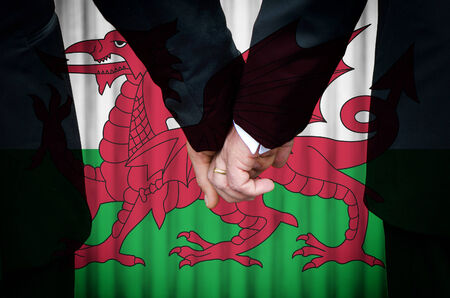 Two gay men stand hand in hand before a marriage altar featuring an overlay of the flag colors of Wales, having just been legally married under the Same-Sex Marriage legislation of that country.    photo