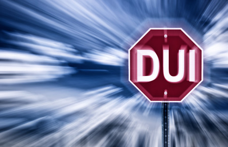 Stop-Schild gegen einen stimmungsvollen Himmel mit den Buchstaben DUI aufgedruckt. Das Bild ist verwackelt, um Bewegung verschwommenes Sehen aufgrund Intoxikation implizieren. Standard-Bild - 28267564