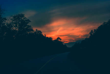 A dusky sunset along a paved road through a forested area featuring silhouetted trees against a moody orange sky   Processed and toned for a vintage faded retro look Imagens - 28270368