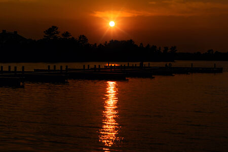 muskoka: The sun setting over a lake with empty docks on the water   Silhouetted trees are seen in against the orange sky  Stock Photo
