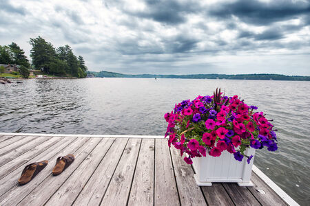 A cottage scene of a dock on the lake with a planter of petunias and a pair of Sandals   There is a boat in the distance  photo