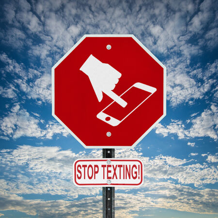 A red stop sign with a symbol of a hand texting on handheld smartphone device and the words stop texting written on a sign bellow   Sign is against a blue sky with some clouds  Symbol is artist own conceptual design  photo