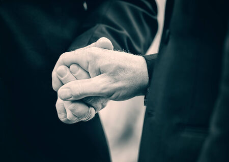 A close up of two married men holding hands at their wedding   Lightly Toned  Stock fotó