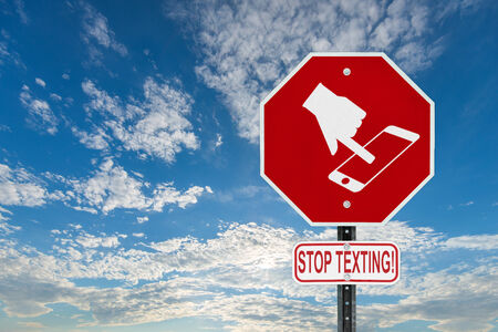 A red stop sign with a symbol of a hand texting on handheld smartphone device and the words stop texting written on a sign bellow    photo